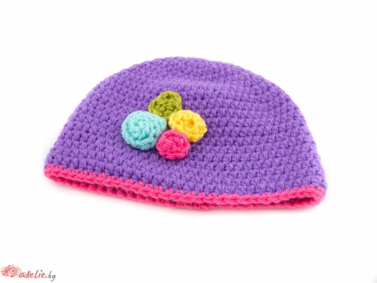 Ръчно изплетена лилава зимна шапка.
